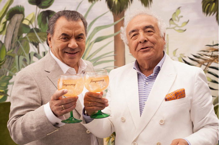 Two older men clinking glasses of Tanqueray against each other