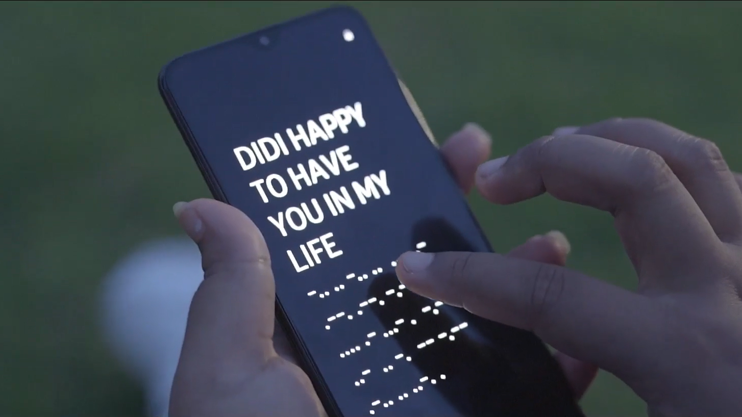 Smartphone screen showing a message, 'DIDI HAPPY TO HAVE YOU IN MY LIFE' and in braille