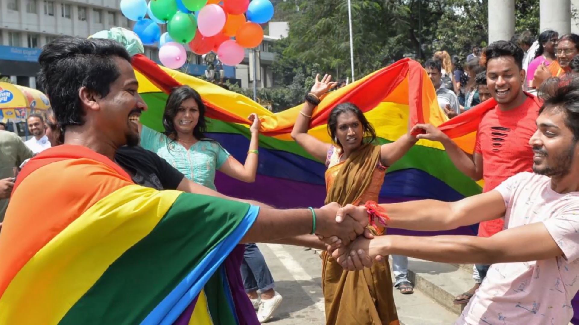Young Indian people dancing, with two men holding hands and draped in a rainbow banner