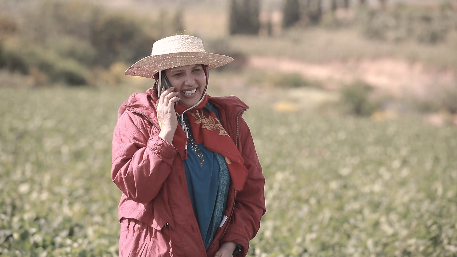 Woman walking in rural area while talking on a mobile phone